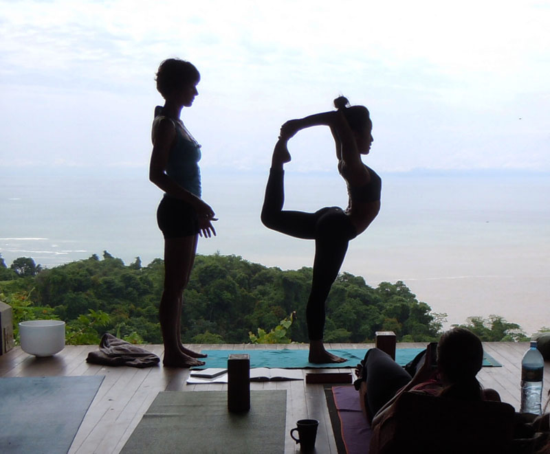 A participant is practicing Lord shivas pose under the guidance of an instructor in Anamaya Yoga Resort