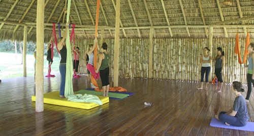 women practicing aerial yoga at wooden yoga deck