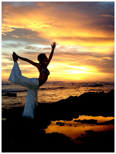 woman doing hatha yoga on sea beach under colorful sky