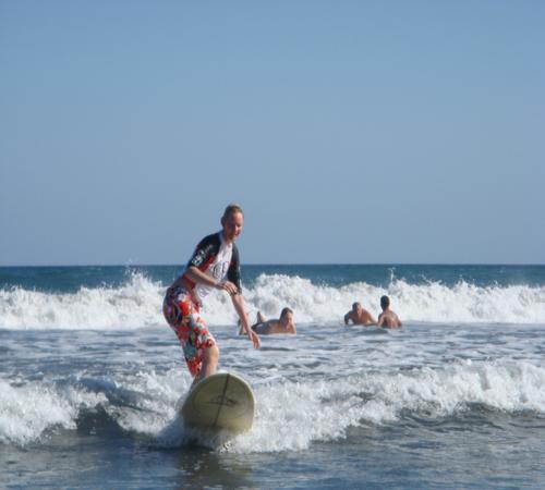 woman surfing on tropical sea beach