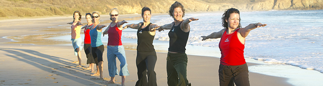 women doing warrior pose on a sea beach