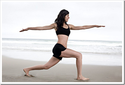 woman doing warrior pose on the beach